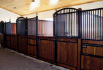 High Stall Front 31: Stall design with bar top; wood bottom; Euro-style center and bottom rails; Dutch-style door; swivel feeder and integrated water lines; and brass ball finials.